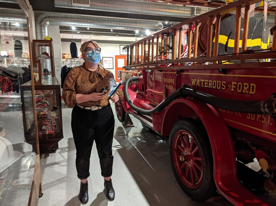 Woman with blonde hair and blue facemask holding a clipboard near an antique firetruck.